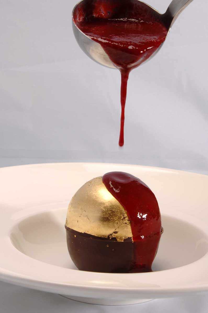 Chocolate Surprise decorated with gold leaf and served with a coulis